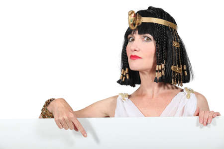 dressing up costume: Cleopatra pointing at blank advertising board Stock Photo