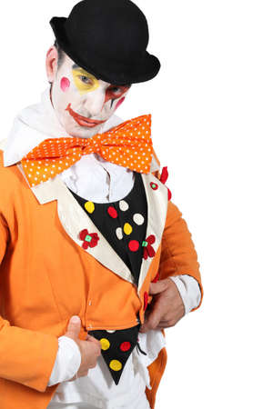 grotesque: man maked up wearing a grotesque clown costume and a bowler