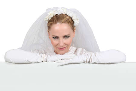 duplicitous: Woman in a bridal gown leaning on a white board