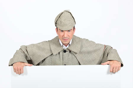 sherlock: Man in deerstalker and cape leaning on a white board ready for your text Stock Photo