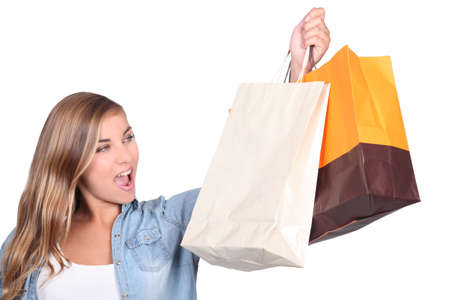 retail therapy: Blond woman stood holding shopping bags Stock Photo