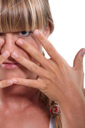 hiding face: Young fair-haired woman hiding her face behind her hands Stock Photo