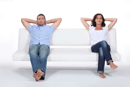 angry couple: Couple sitting on white sofa