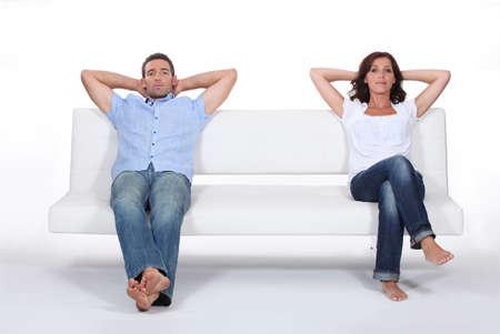 pareja enojada: Pareja sentada en el sofá blanco Foto de archivo