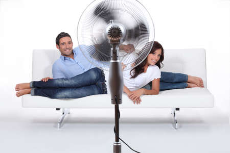 hot couple: Man and woman laid on a sofa being ventilated by fan