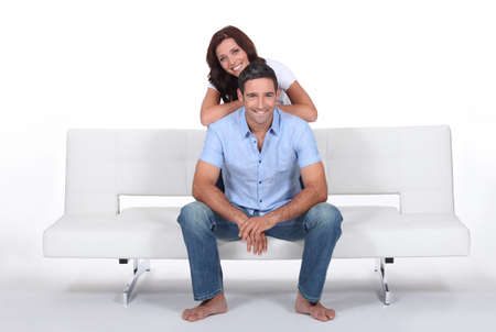 woman on couch: Smiling couple on a sofa, studio shot