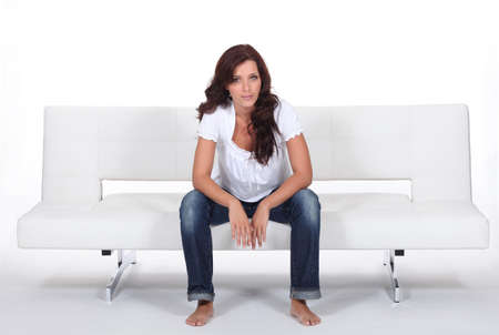 Casually dressed woman sitting on a white modern bed settee photo