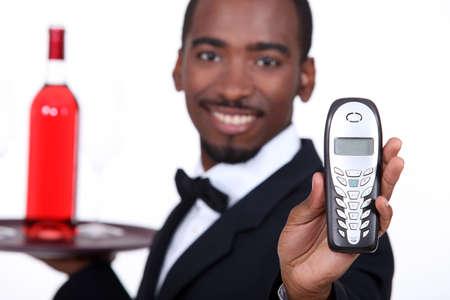 Restaurant waiter holding telephone photo