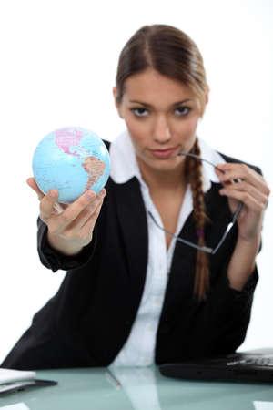 Woman holding up a mini-globe Stock Photo - 15807693
