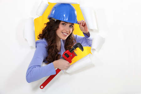 affability: female worker watching us through a hole in a paper wall Stock Photo