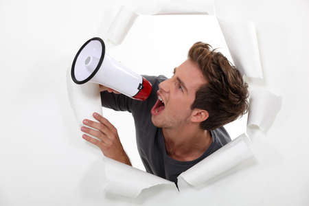 Young man shouting into a megaphone photo