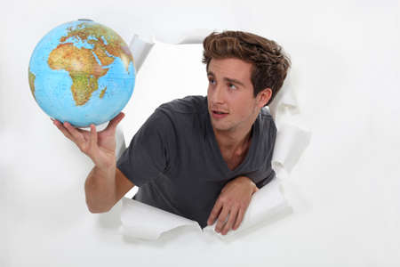 popping out: Man popping out a ripped wall in paper holding a globe  Stock Photo