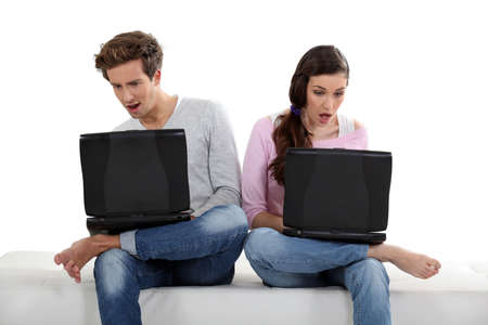Shocked couple looking at laptops photo