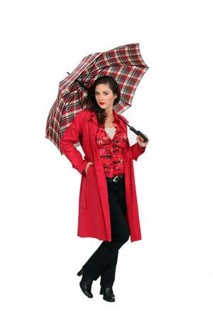 drizzling rain: A fashionable woman holding an umbrella