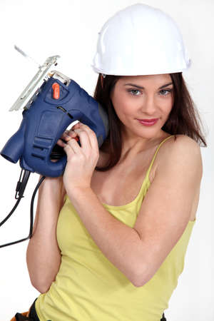 foxy female carpenter holding sander machine photo