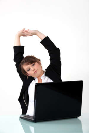 end of time: Businesswoman sat at desk stretching