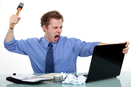 Executive about to smash his laptop with a hammer