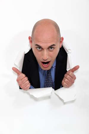 bald spot: Man peeking through torn paper hole