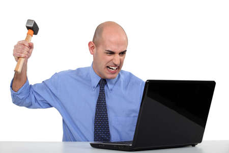 Businessman taking a hammer to his laptop photo