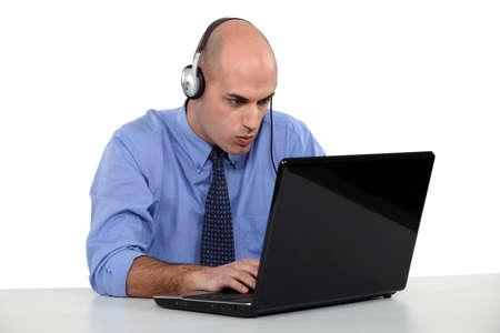 Businessman wearing headphones typing on laptop photo