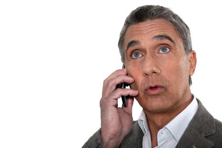 nervousness: Confused man making telephone call Stock Photo