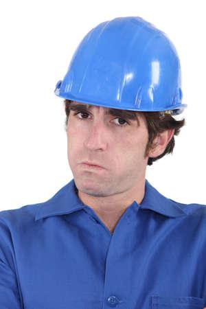 infuriate: head-and-shoulders portrait of craftsman looking exasperated