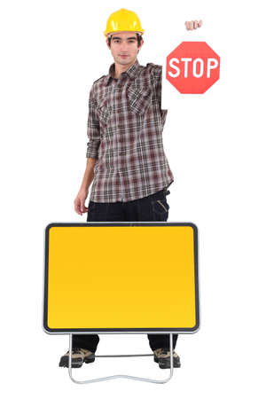 young bricklayer holding stop sign isolated on white photo