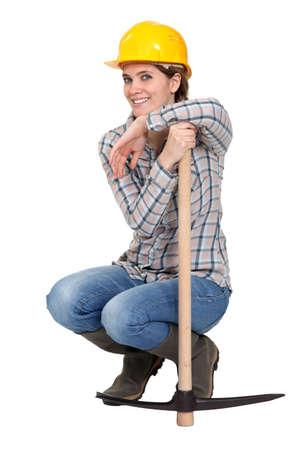 donna in ginocchio: Donna inginocchiata con un piccone Archivio Fotografico