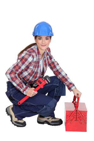 A female construction worker holding a wrench  photo