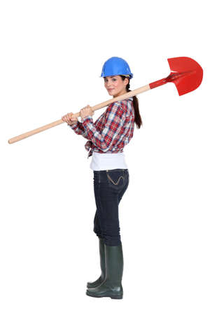 yard work: Female manual worker carrying shovel Stock Photo