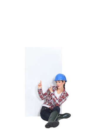 holding blank sign: Female construction worker pointing at copyspace