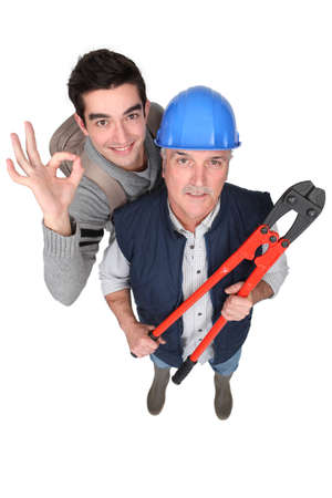Builder and apprentice stood with bolt cutters Stock Photo - 15832825