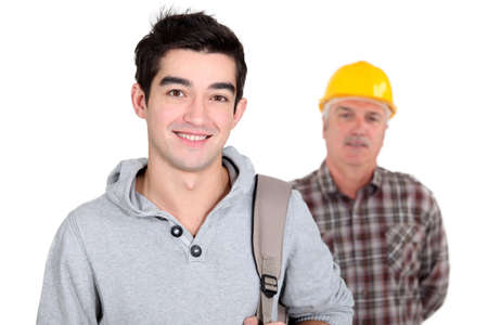 younger: Young man standing next to an experienced worker
