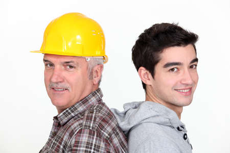 co operative: Tradesman standing back to back with his apprentice Stock Photo