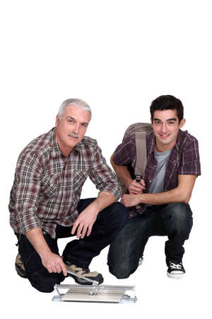 TIler and young teenage apprentice Stock Photo - 15832935