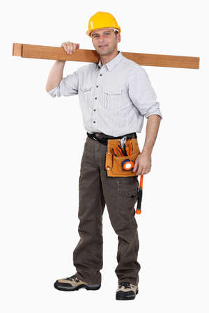 A carpenter carrying planks  photo