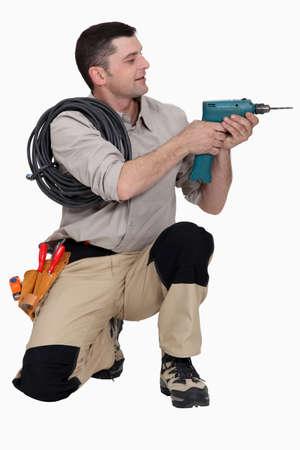 arrodillarse: Tradesman sosteniendo un destornillador eléctrico Foto de archivo