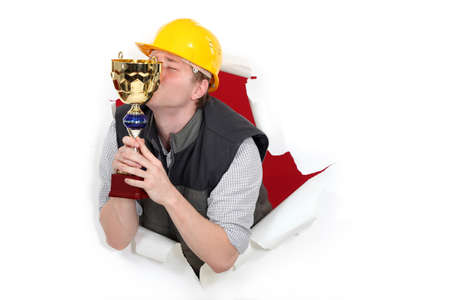Construction worker kissing a trophy photo