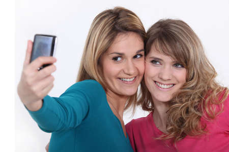 Two girls taking a picture with a mobile phone photo