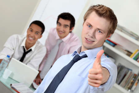 Young businessman giving thumbs-up during meeting photo