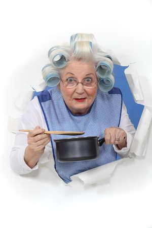 Elderly lady stirring sauce pan photo