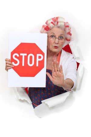 Eine alte Dame mit einem Stop-Schild