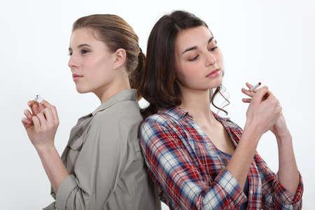 joven fumando: Chica encendiendo un cigarrillo mientras otro encaje en un medio Foto de archivo