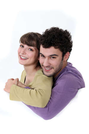 enraptured: A loving young couple cuddling Stock Photo