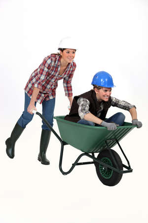 barrow: Two female construction workers racing in a wheelbarrow