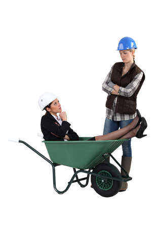 workwoman: Unhappy tradeswoman distraught at finding an engineer in her wheelbarrow Stock Photo
