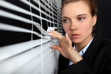 Woman looking through blinds photo