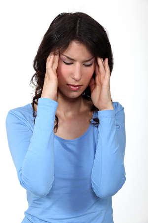 worried woman: A young brunette having a headache