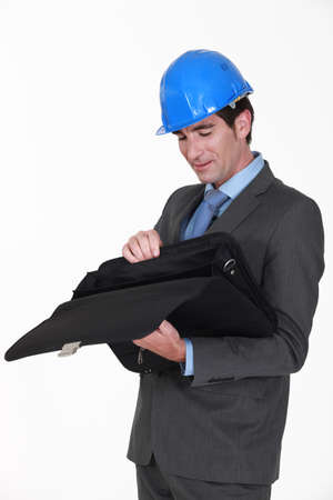 40 something: Engineer looking for something in his briefcase Stock Photo