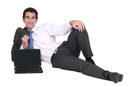 laid back: Businessman lying on the floor with his laptop Stock Photo